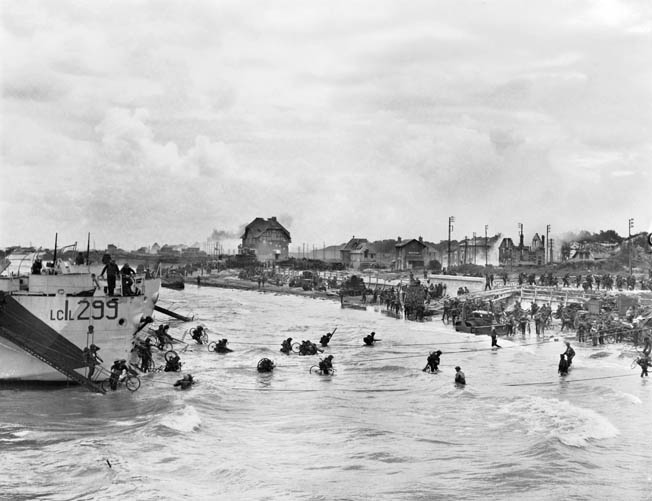"With the beachhead relatively secure, second-wave troops of the Highland Light Infantry, 9th Canadian Infantry Brigade disembark with bicycles from LCI(L)s (Landing Craft Infantry, Large) onto Juno Beach, ""Nan White"" Sector, at Bernières-sur-Mer, shortly before noon on June 6."