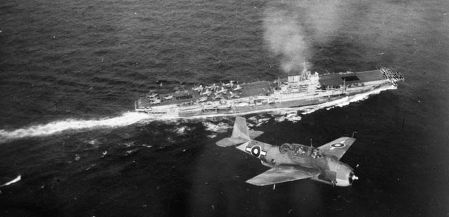 A British-marked Grumman TBM Avenger aircraft of the Fleet Air Arm, returning from an attack on Sakishima Gunto, flies above the HMS Indomitable in March 1945.