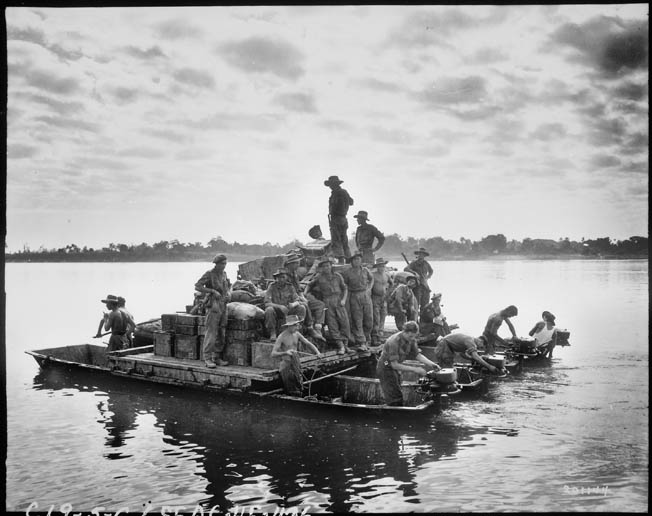 British troops, their truck, and boxes of ammunition cross the Irrawaddy River on a raft, February 14, 1945. The British had assembled 120 boats and 17 rafts for the crossing and despite difficulties, most of 33rd Brigade was transferred to the east bank by the end of the day.