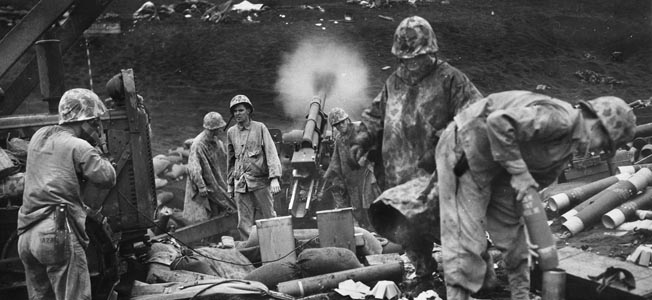 Artillerymen of the 4th Marine Division use a 105mm howitzer to blast Japanese positions.