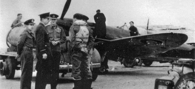 Chief Air Marshal Charles Portal, second from left, and Air Vice Marshal Keith Park, third from left, talk with fighter pilots while a Spitfire is fueled.