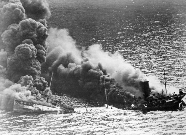 Its back broken, an oil tanker bound for Britain billows smoke as it sinks into the depths of the Atlantic Ocean. German submarines torpedoed Allied shipping at an alarming rate during Operation Drumbeat, forcing the U.S. Navy to employ new methods of antisubmarine warfare to keep the tenuous supply line open.
