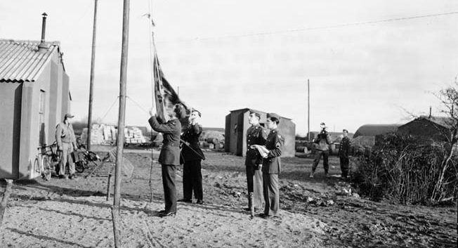 United States Army Air Forces personnel replace the British Union Jack with the U.S. Stars and Stripes after taking over the former Royal Air Force base at Bedford, England, in 1942. Bib Bowers arrived in Bedford in 1944 to begin his tour of 30 bombing missions over Nazi-occupied Europe.