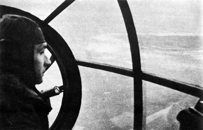 A crewman of a German Heinkel He-111 looks down on the Lyness Naval Base on the island of Hoy, Orkney Islands, October 18, 1939. German raids caused the British to strengthen their bases and disperse their fleet and facilities.