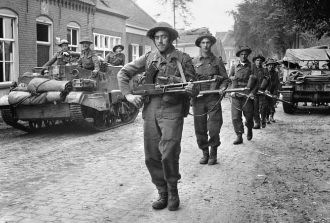 A British soldier carrying a 22-pound Bren gun leads an 11th Armoured Division patrol of infantrymen and Universal carriers through Deurne, Belgium, in September 1944.