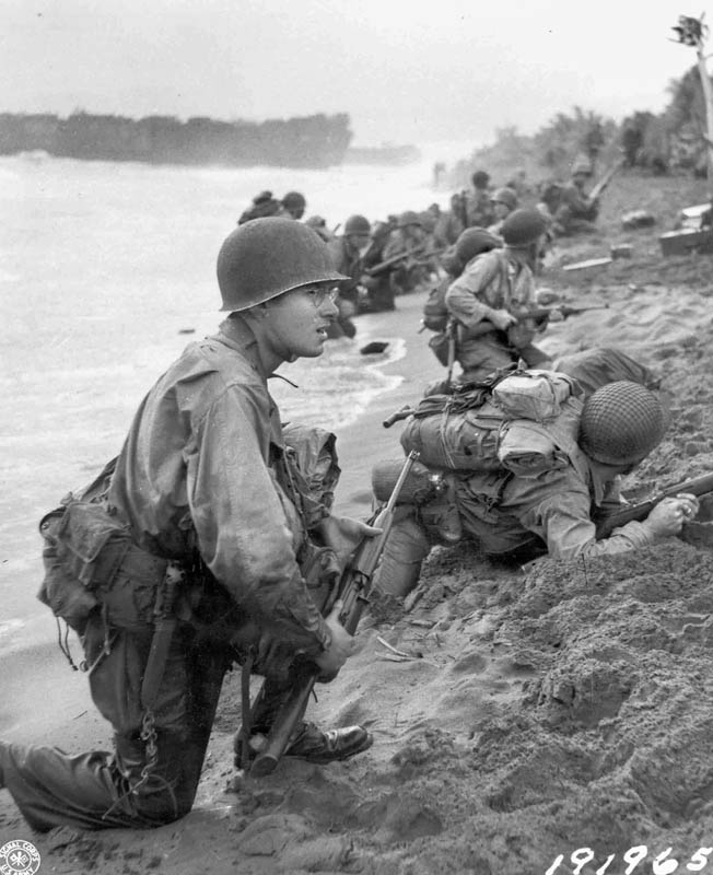 American soldiers of the 32nd Infantry Division slog through a river while on patrol in the Aitape region of New Guinea. American offensive action cut off a sizable Japanese force, and the fight at the Driniumor River ensued.