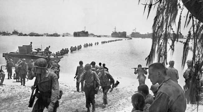Reinforcing the Marines that are already fighting on Saipan, these soldiers of the U.S. Army's 27th Infantry Division file forward from their LSTs (landing ship, tank). The LSTs were required to anchor on the other side of a coral reef, and the soldiers had to wade ashore through the surf.