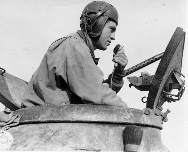A tank commander of the American 4th Infantry Division uses his radio to determine the positions of other tanks in his unit. Superior radio communications provided a distinct advantage for the Americans in combat.