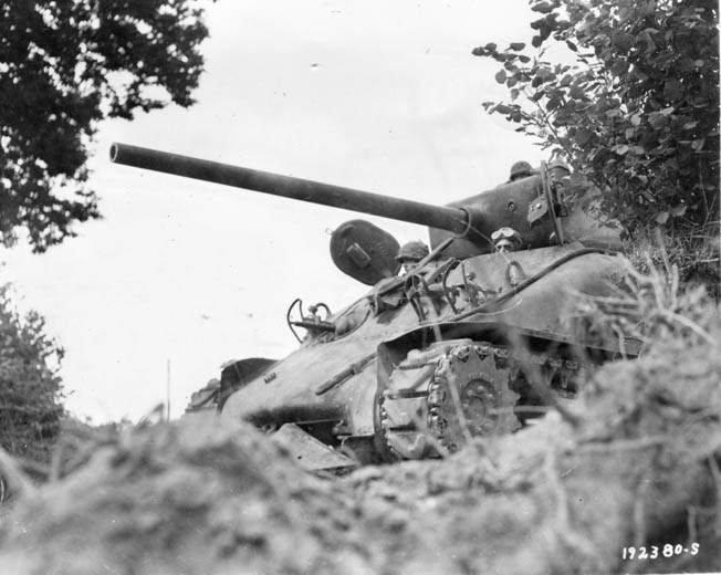 American crewmen peer from the chassis of their M4 Sherman tank somewhere in France. This Sherman mounts a 76mm gun, a higher velocity weapon than the original 75mm cannon that equipped the M4. The 76mm gun was nicknamed the 'hole puncher.'