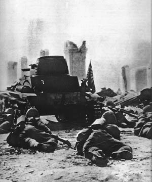 Japanese infantrymen crawl behind a tank through a shattered street during the Battle of Singapore, early February 1942.
