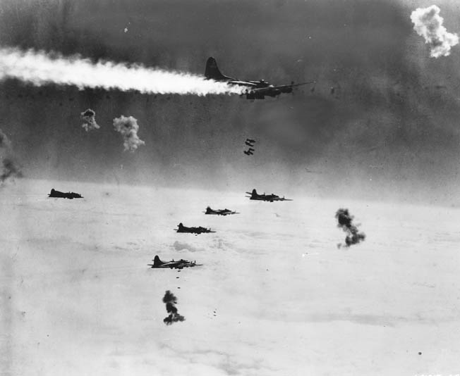 Despite an engine and starboard wing on fire, a B-17 stays in formation to drop its bombs during an earlier attack on Berlin. Note the antiaircraft explosions around the formation.