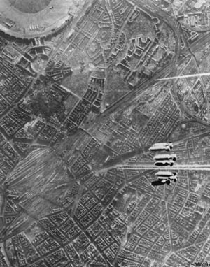 Bombs away! A salvo of 500-pound bombs hurtles toward a rail yard near the center of Berlin, February 3, 1945. Note that almost all the buildings below have no roofs.