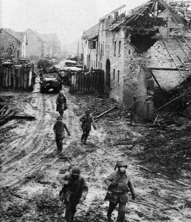 A battleworn column of American troops makes its way through the remains of a village in the Ardennes.
