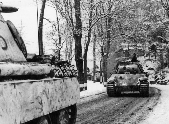 German PzKpfw. V Panther medium tanks roll along a muddy road silhouetted against a winter landscape during the early hours of the Ardennes Offensive. Walter's 3rd Platoon, Company L, 3rd Battalion, 393rd Infantry Regiment hunkered down for hours beside an unpaved road as German tanks and infantry streamed past.
