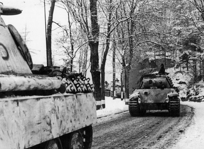 Camouflaged with white paint, German tanks traverse an icy road toward the River Meuse and a date with destiny.