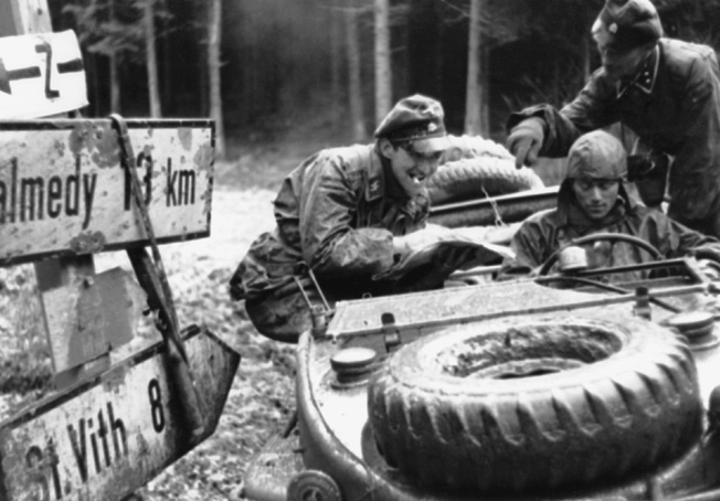 Caked with mud and accompanied by a German war correspondent, an officer and driver belonging to Kampfgruppe Peiper examine a map to determine their next move.