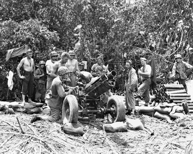 Marines from Battery H, 12th Marine Artillery Regiment, 3rd Marine Division load a 75mm pack howitzer in preparation for a fire mission just inland off Blue Beach 2.
