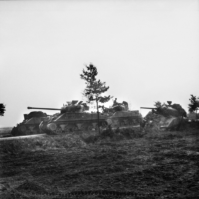 """An up-gunned Sherman """"Firefly"""" tank of the Irish Guards rolls past three other tanks knocked out during Operation Market-Garden on September 17, 1944."""