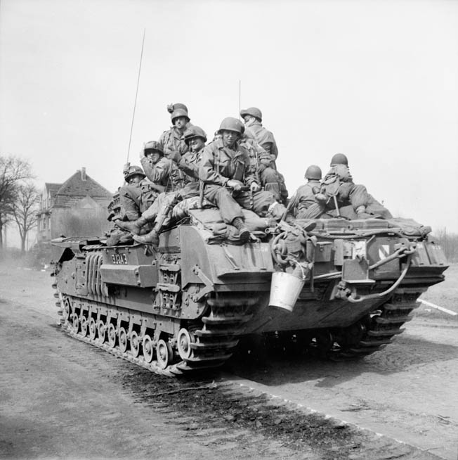 Men of the 17th Airborne Division ride atop a Churchill tank belonging to the 6th Guards Tank Brigade through Dorsten, Germany, east of Wesel.