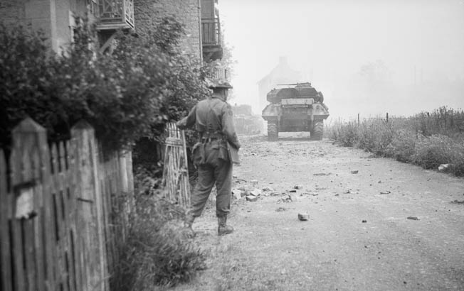 Typically disregarding his personal safety, Lt. Col. James L. Moulton, commander of 48 Commando, watches a Canadian M-10 tank destroyer approaching a disabled Royal Marine Centaur tank (in the distance) during the attack on the strongpoint known as WN 26 at Langrune.