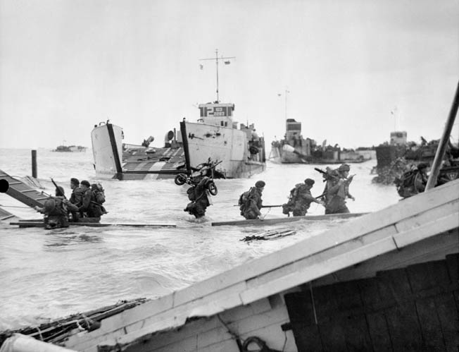 With one man carrying a small motor scooter on his shoulder, men of 48 Commando disembark from landing craft at Juno Beach near St.-Aubin-sur-Mer, June 6, 1944.