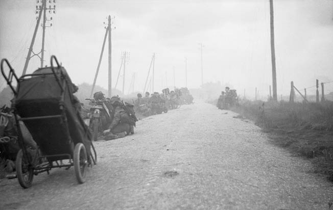 Men from 48 Commando and Canadian infantry with their bicycles take cover from German mortar fire in ditches near St.-Aubin-sur-Mer.