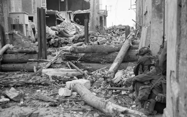 Canadian infantrymen from the North Shore (New Brunswick) Regiment cautiously approach another German strongpoint, WN 27, at St.-Aubin-sur-Mer.