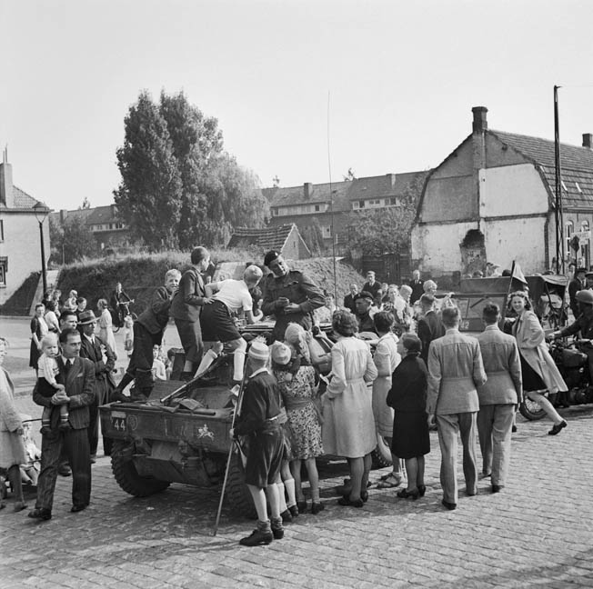 Dutch civilians celebrate their liberation, gathering around an armored vehicle of the British Guards Armored Division as the ground troops pass through the village of Grave, Holland. The ground forces have just linked up with troopers of the 82nd Airborne Division.