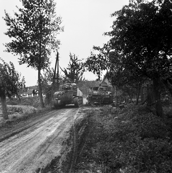 A Sherman tank of the 47th/7th Dragoon Guards passes a knocked-out German PzKpfw III in Oosterhout near Nijmegen, September 27, 1944. Narrow roads such as this hampered Allied efforts to reinforce the bridgeheads.