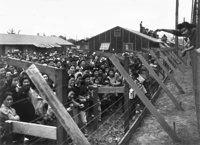 In a scene reminiscent of German concentration camps, Japanese Americans behind barbed wire at their camp at Santa Ana, California, wave farewell to friends on a train (right).