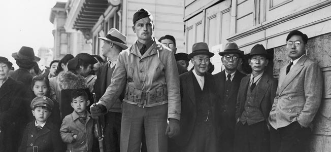 CALIFORNIA, UNITED STATES - APRIL 29:  Forlorn looking American soldier standing guard in front of some Japanese American citizens awaiting transport to relocation camps after they were forcebly rounded up from their homes all along the west coast.  (Photo by Dorothea Lange/National Archives/Time & Life Pictures/Getty Images)