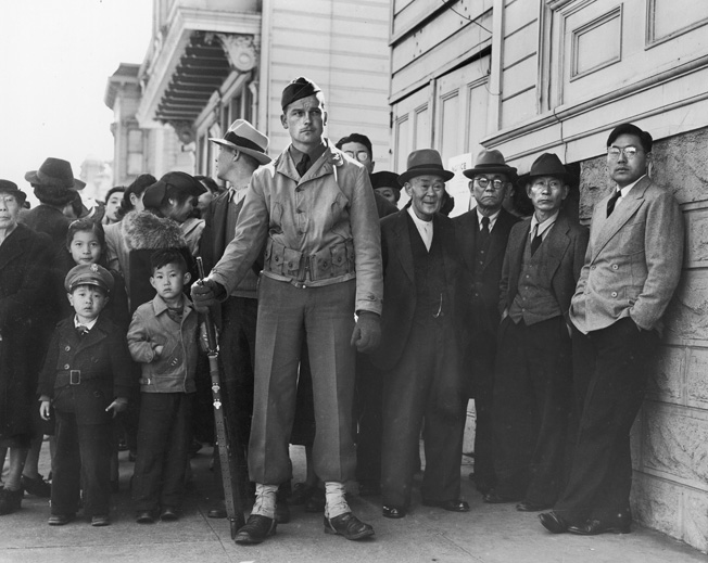 In this photo by famed Depression-era photographer Dorothea Lange, Japanese American families in  San Francisco, California, watched over by a single armed U.S. solder, wait to register for government-mandated forced relocation, April 1942.