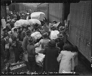Japanese Americans scramble to load all the personal possessions they can carry into a train leaving for the war-relocation camp at Manzanar, California.