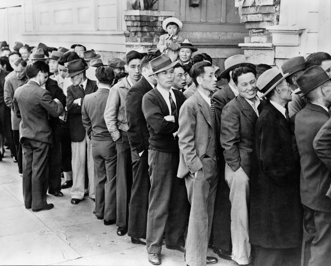 Displaying a variety of emotions, Japanese Americans wait in line at the Civil Control Station in San Francisco to register as required for relocation, April 1942.