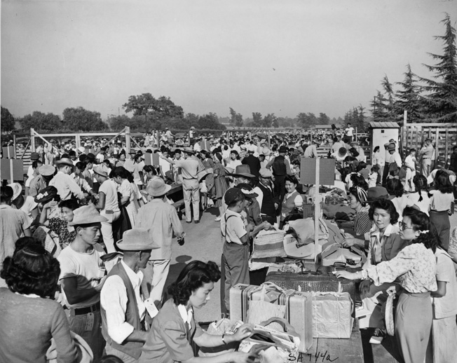 Nisei gather at an assembly area established at the Santa Anita Race Track in Arcadia prior to being shipped against their wishes to relocation centers. Efforts were made, however, to keep families—and even neighbors—together.