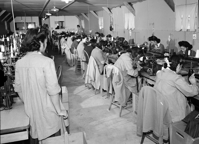 "Renowned photographer Ansel Adams documented life at Manzanar. Here, Sumiko Shigematsu (left) supervises a hut full of ""power sewing machine girls"" making clothes for the internees."
