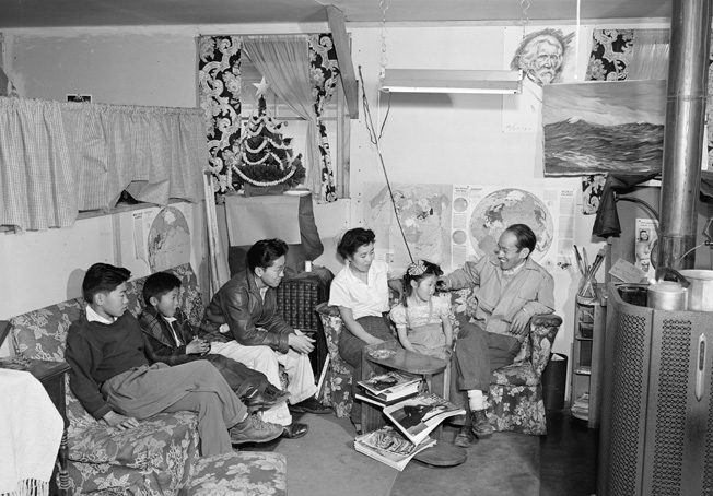"above: This family at Manzanar, photographed by Ansel Admas, tried to make their cramped, drafty quarters as comfortable and ""homelike"" as possible, but there was no disguising the physical and mental hardships the internees suffered. opposite: Estelle Ishigo, a European American, accompanied her Nisei husband to the Heart Mountain Camp in Wyoming, where she painted this scene depicting ""home"" in one of the Spartan barracks."