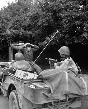 "Two Germans surrender to 6th Armored Division troops during the American advance into Brittany. The soldier in the jeep is wielding a .45-caliber ""grease gun"" submachine gun."