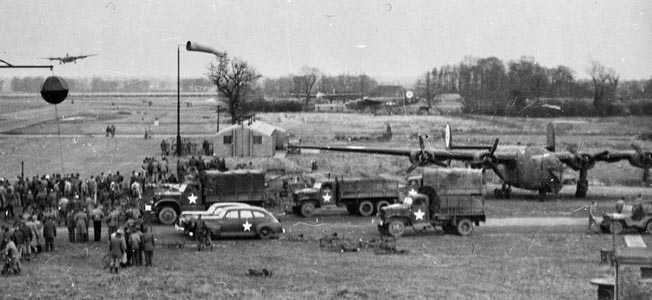 A crowd of onlookers has gathered with its accompanying trucks and staff cars to watch the approach of an overdue Consolidated B-24 Liberator at an airbase in England. The B-24 proved an excellent aircraft in the anti-submarine role and was also one of the primary aircraft deployed during the Allied strategic bombing campaign against Nazi Germany.