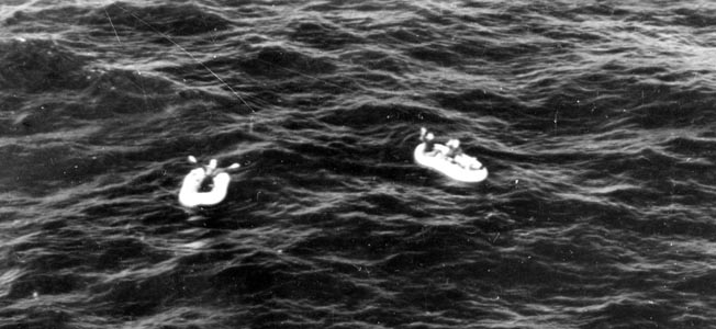 Three Allied crewmen, believed to be from a B-24 bomber piloted by Lieutenant Charles Moore, wave to rescue aircraft from their rafts in the open Atlantic. Their B-24 was shot down by a German Ju-88 over the Bay of Biscay.