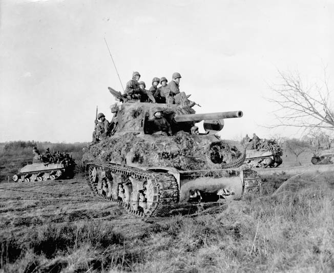 rymen ride into battle atop a foliage-covered Sherman tank near Freyneux in December 1944.