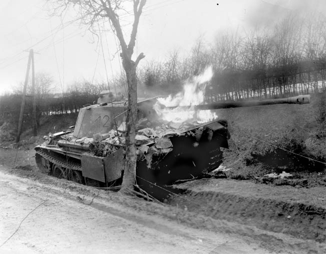 With its turret and 75mm main gun reversed, a German Panzer V Panther tank, similar to Langanke's, burns after being struck by an Sherman tank round during fighting in Belgium in December 1944. Chunks of stone and masonry on the tank's back deck indicate it may have crashed through a wall or a building.