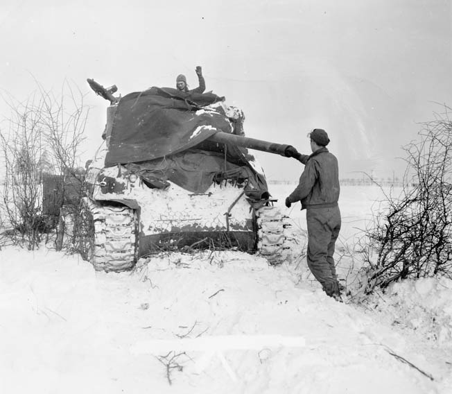 American tankers clean the bore of their M-4 Sherman's 76mm gun during a pause in the battle. The frigid, snowy weather added to the difficulties both sides faced.