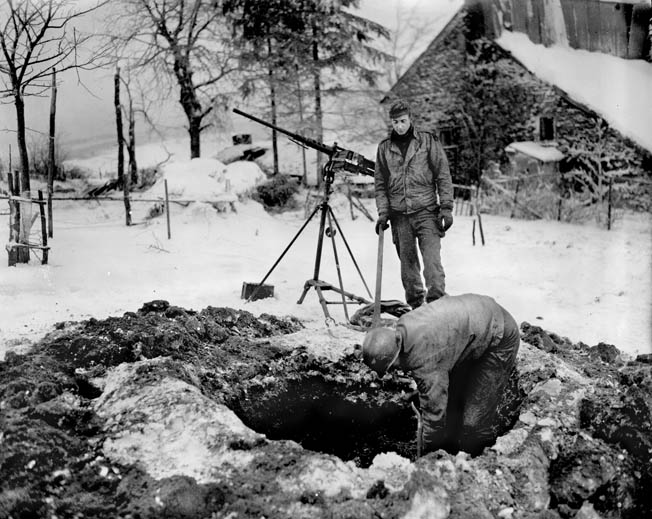 Artillerymen dig a gun emplacement into the frozen soil of a Belgium farm near the village of Freyneux.