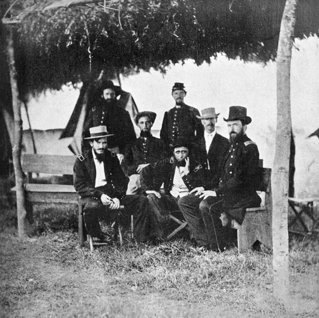 Grierson, seated center with hand on chin, is surrounded by his staff.