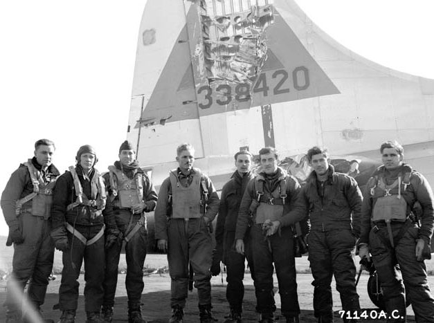 A B-17 Flying Fortress crew stands in front of battle damage to the vertical tail fin of Betty Jane, their Boeing B-17G Flying Fortress 43-38420 of the 526th Bombardment Squadron, 379th Bombardment Group at RAF Kimbolton, England in late 1944.