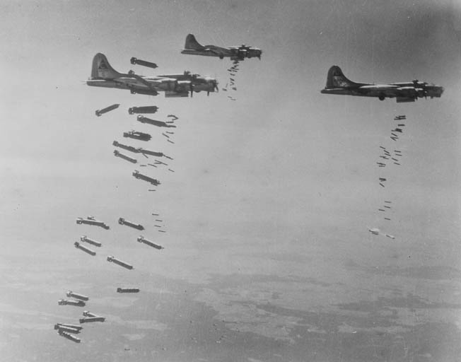 B-17G Flying Fortresses of the 750th Bombardment Squadron, 457th Bombardment Group, drop their bombs on a mission over Germany. By flying in tight formations, the B-17's machines guns could provide mutually supporting defensive fire against enemy fighters.