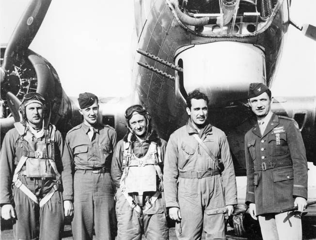 """A weary B-17 crew poses with their group commander following a mission in Europe. The twin .50-caliber M2 machine guns in the nose """"chin"""" turret are stowed in the safe position, pointing upward and to the side."""