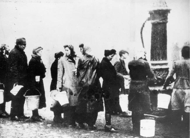 Hundreds of Allied bombing raids completely destroyed Berlin's infrastructure. Here, Berlin women line up to draw water from one of the city's few working fountains.