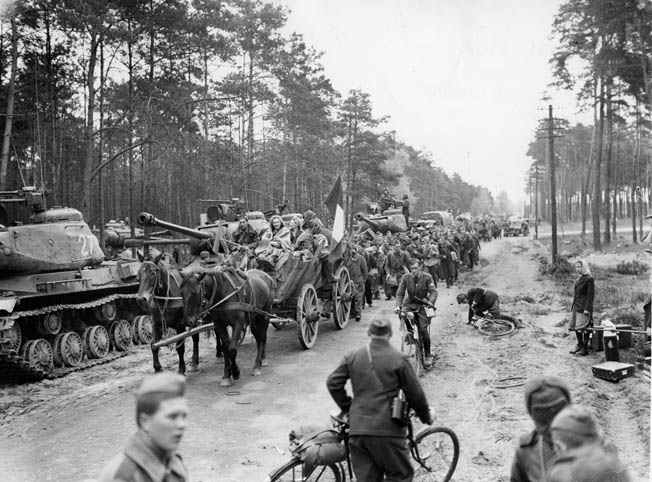 Desperate to flee the battle for Berlin, German civilians and freed Allied prisoners of war head westward past a column of Soviet tanks and toward American forces.